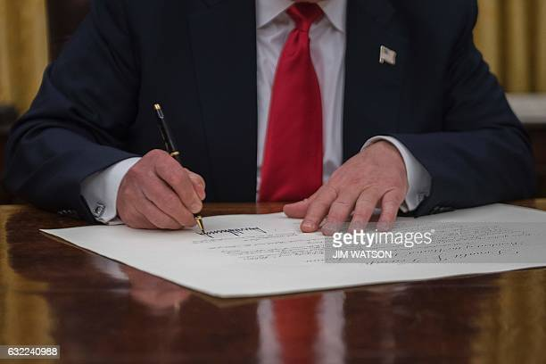 US President Donald Trump signs a conformation for General John Kelly as US Secretary of Homeland Security in the Oval Office of the White House in...