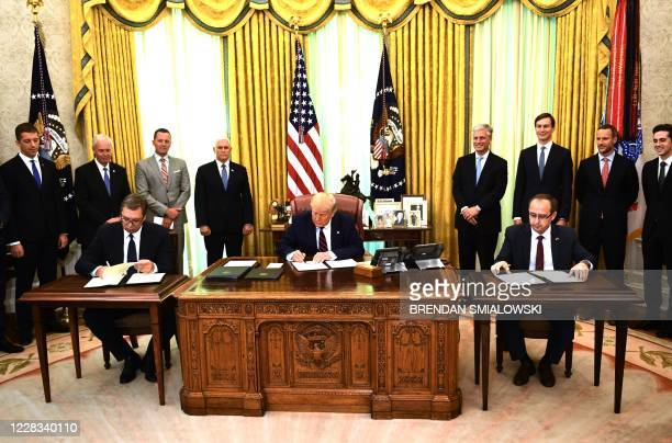 President Donald Trump signs a document as Kosovar Prime Minister Avdullah Hoti and Serbian President Aleksandar Vucic sign an agreement on opening...