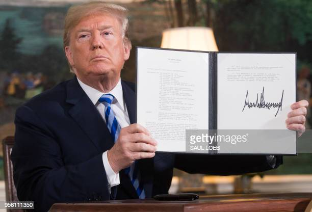 President Donald Trump signs a document reinstating sanctions against Iran after announcing the US withdrawal from the Iran Nuclear deal, in the...
