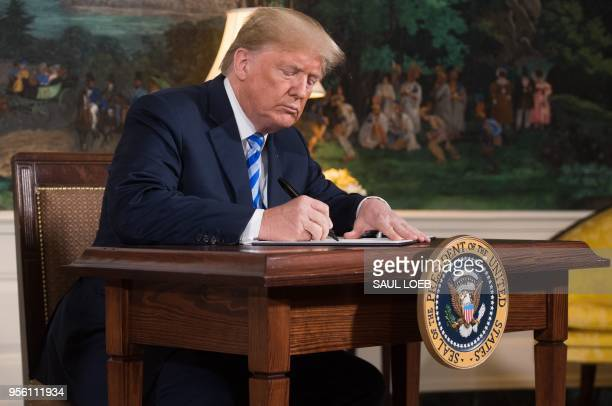 US President Donald Trump signs a document reinstating sanctions against Iran after announcing the US withdrawal from the Iran Nuclear deal in the...