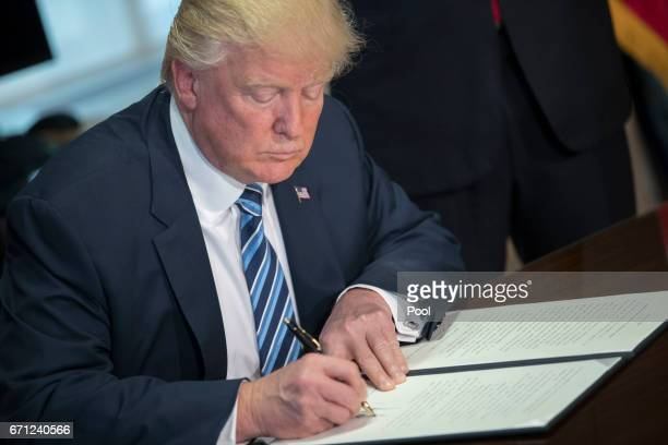 President Donald Trump signs a financial services Executive Order during a ceremony in the US Treasury Department building on April 21, 2017 in...