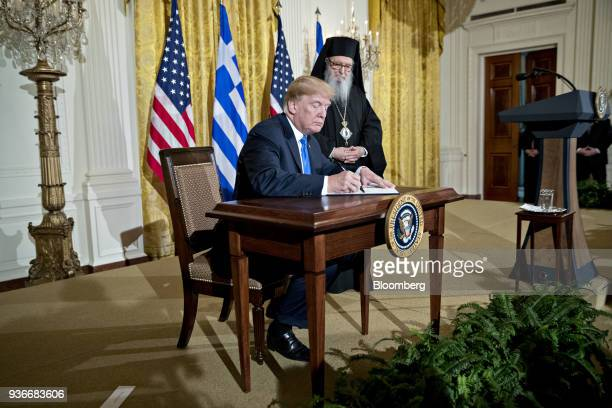 US President Donald Trump signs a Greek Independence Day proclamation next to Archbishop Demetrios of America elder archbishop of the Greek Orthodox...