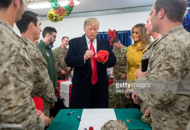 US President Donald Trump signs a hat as First Lady Melania Trump looks on as they greet members of the US military during an unannounced trip to Al...