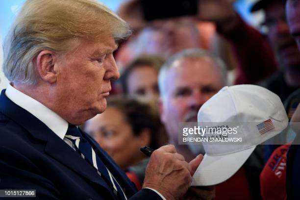 US President Donald Trump signs a hat while meeting with supporters during a Bikers for Trump event at the Trump National Golf Club August 11 2018 in...