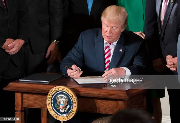 President Donald Trump signs a letter of initiative to privatize the nation's air traffic control system during an event in the East Room of the...