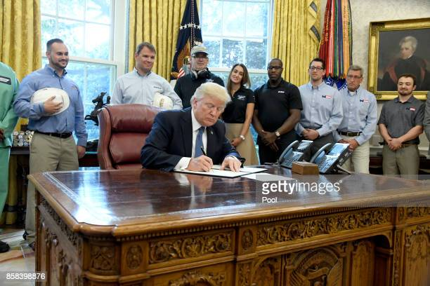 US President Donald Trump signs a National Manufacturing Day Proclamation in the Oval Office of the White House on October 6 2017 in Washington DC