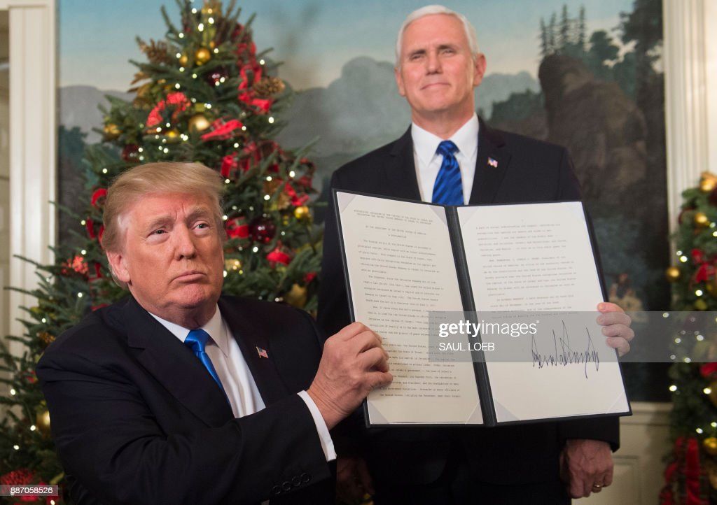 US President Donald Trump signs a proclamation after he delivered a statement on Jerusalem from the Diplomatic Reception Room of the White House in Washington, DC on December 6, 2017 as US Vice President Mike Pence looks on. President Donald Trump on Wednesday recognized the disputed city of Jerusalem as Israel's capital -- a historic decision that overturns decades of US policy and risks triggering a fresh spasm of violence in the Middle East.'I have determined that it is time to officially recognize Jerusalem as the capital of Israel,' Trump said from the White House.'It's the right thing to do.' LOEB