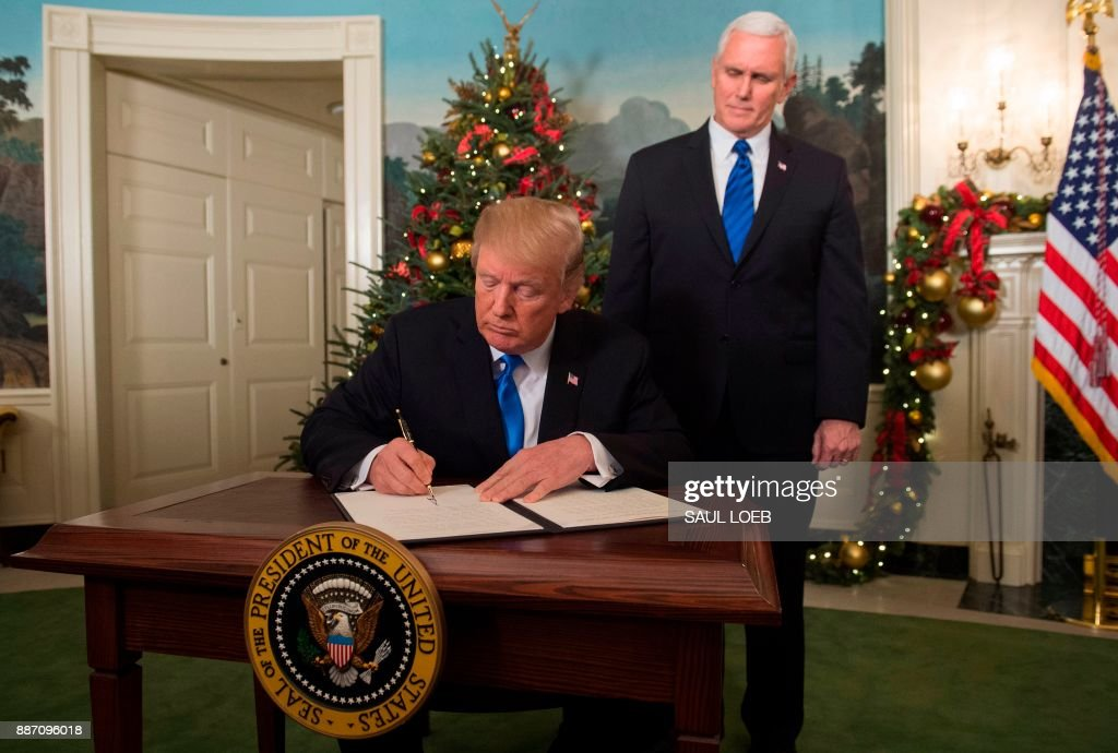 President Donald Trump signs a proclamation after he delivered a statement on Jerusalem from the Diplomatic Reception Room of the White House in Washington, DC on December 6, 2017 as US Vice President Mike Pence looks on. President Donald Trump on Wednesday recognized the disputed city of Jerusalem as Israel's capital -- a historic decision that overturns decades of US policy and risks triggering a fresh spasm of violence in the Middle East.'I have determined that it is time to officially recognize Jerusalem as the capital of Israel,' Trump said from the White House.'It's the right thing to do.' /