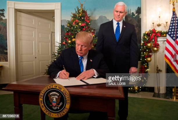 President Donald Trump signs a proclamation after he delivered a statement on Jerusalem from the Diplomatic Reception Room of the White House in...
