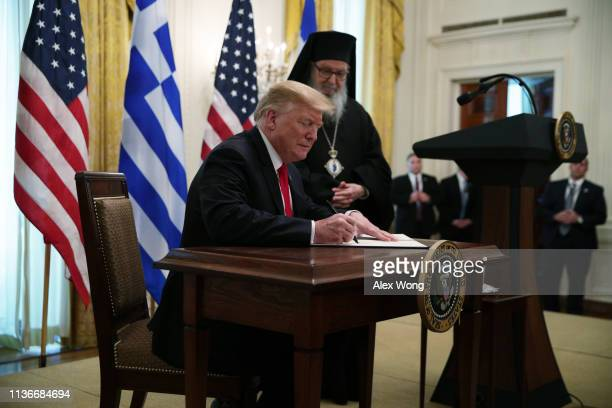 US President Donald Trump signs a proclamation as Archbishop Demetrios Geron of America looks on in a Greek Independence Day celebration at the East...