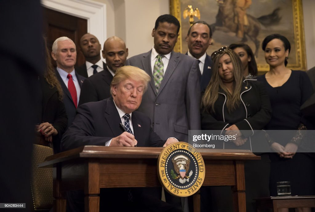 U.S. President Donald Trump signs a proclamation for Martin Luther King Jr. Day in the Roosevelt Room of the White House in Washington, D.C., U.S., on Friday, Jan. 12, 2018. Trump blew up negotiations on a potential immigration deal, pushing both sides to harden their positions and raising the risks that the standoff will sink talks aimed at averting a government shutdown at the end of next week. Photographer: Eric Thayer/Bloomberg via Getty Images