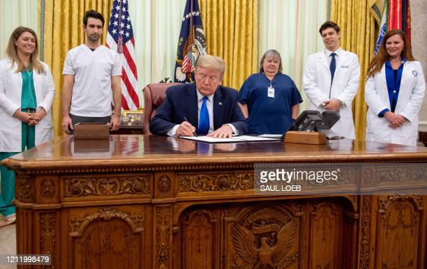 US President Donald Trump signs a Proclamation in honor of National Nurses Day in the Oval Office of the White House in Washington DC May 6 2020