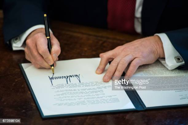 President Donald Trump signs an executive memorandum on investigation of steel imports before signing the document in the Oval Office of the White...