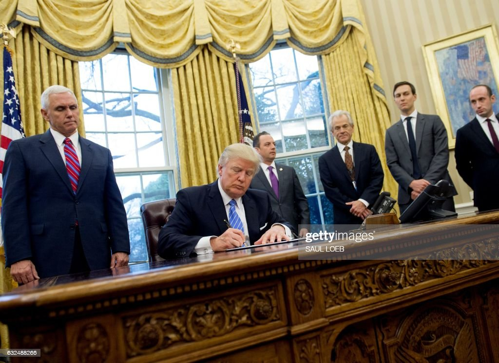 President Donald Trump signs an executive order alongside White House Chief of Staff Reince Priebus (C), US Vice President Mike Pence (L), National Trade Council Advisor Peter Navarro (3rd R), Senior Advisor Jared Kushner (2nd R) and Senior Policy Advisor Stephen Miller in the Oval Office of the White House in Washington, DC, January 23, 2017. Trump on Monday signed three orders on withdrawing the US from the Trans-Pacific Partnership trade deal, freezing the hiring of federal workers and hitting foreign NGOs that help with abortion. /