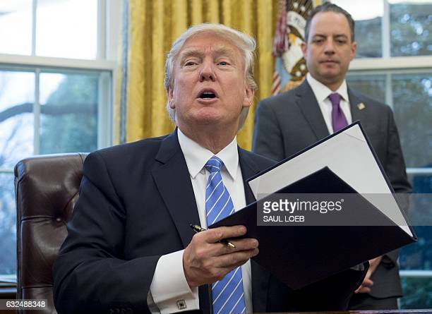 US President Donald Trump signs an executive order alongside White House Chief of Staff Reince Priebus in the Oval Office of the White House in...