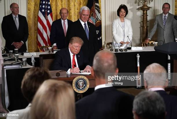S President Donald Trump signs an executive order as Director of National Intelligence Dan Coats Secretary of Commerce Wilbur Ross Vice President...