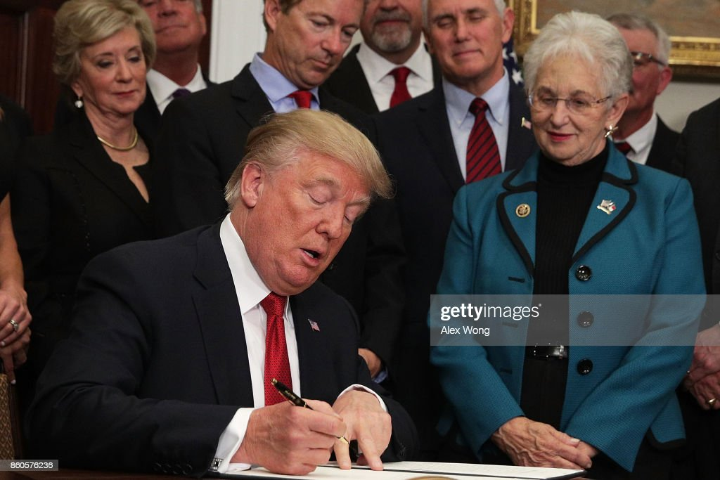 U.S. President Donald Trump signs an executive order as Sen. Rand Paul (R-KY), Vice President Mike Pence, and Rep. Virginia Foxx (R-NC) look on during an event in the Roosevelt Room of the White House October 12, 2017 in Washington, DC. President Trump signed the executive order to loosen restrictions on Affordable Care Act 'to promote healthcare choice and competition.'