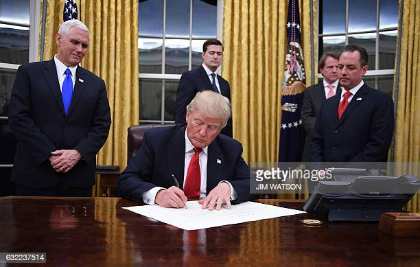 US President Donald Trump signs an executive order as Vice President Mike Pence and Chief of Staff Reince Priebus look on at the White House in...