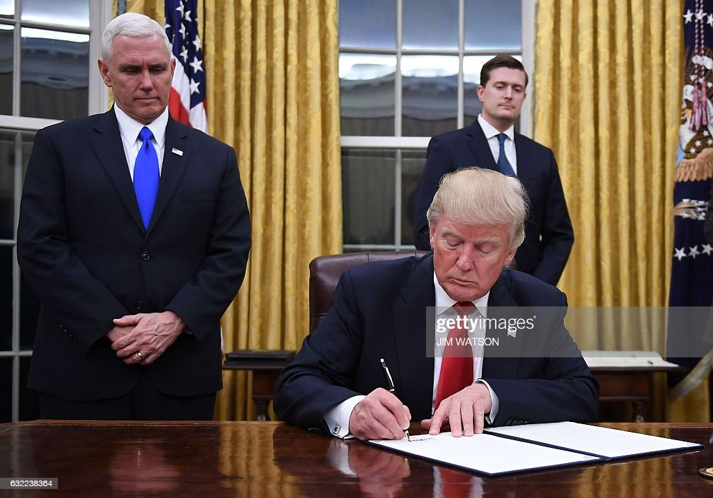 US President Donald Trump signs an executive order as Vice President Mike Pence looks on at the White House in Washington, DC on January 20, 2017. / AFP / JIM