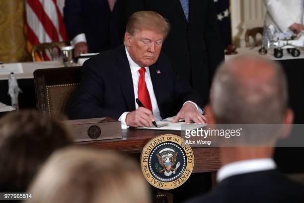 S President Donald Trump signs an executive order during a meeting of the National Space Council at the East Room of the White House June 18 2018 in...