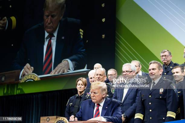 US President Donald Trump signs an executive order during the International Association of Chiefs of Police Annual Conference and Exposition at the...