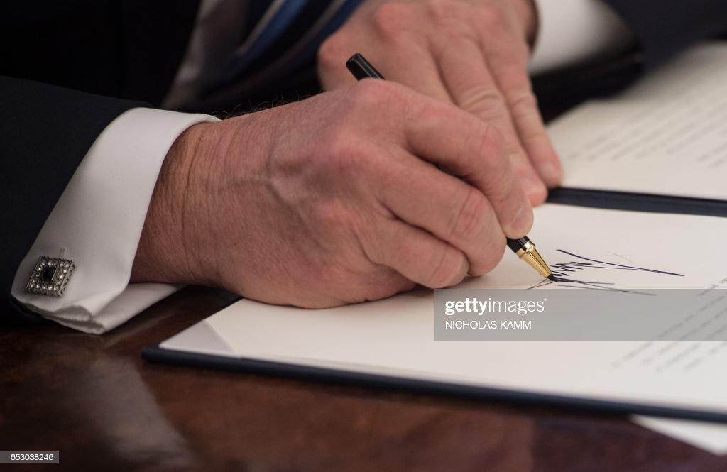 US President Donald Trump signs an executive order entitled Comprehensive Plan for Reorganizing the Executive Branch in the Oval Office at the White House in Washington, DC, on March 13, 2017. /