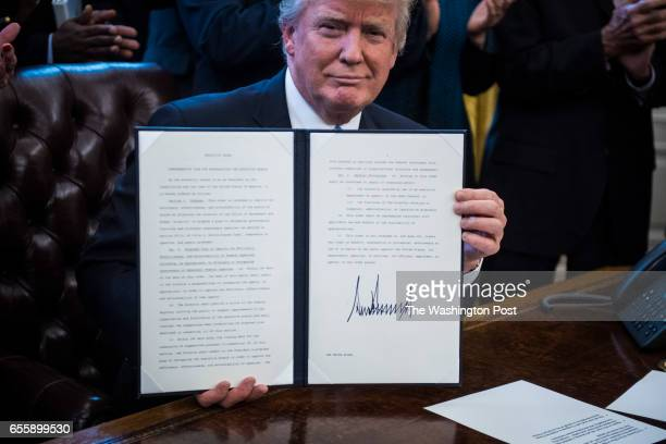 President Donald Trump signs an Executive Order entitled Comprehensive Plan for Reorganizing the Executive Branch in the Oval Office of the White...