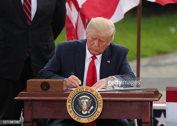 President Donald Trump signs an executive order extending the ban on offshore drilling as he speaks about the environment during a stop at the...