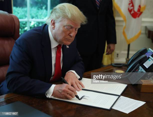 President Donald Trump signs an executive order imposing new sanctions on Iran in the Oval Office at the White House on June 24, 2019 in Washington,...