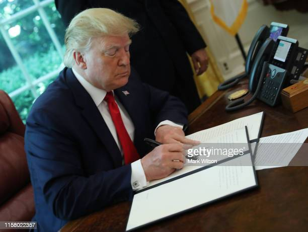 S President Donald Trump signs an executive order imposing new sanctions on Iran in the Oval Office at the White House on June 24 2019 in Washington...