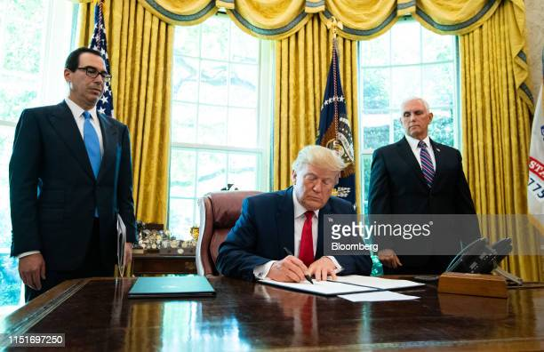 US President Donald Trump signs an executive order imposing sanctions on Iran's supreme leaderAyatollah Ali Khamenei in the Oval Office of the White...