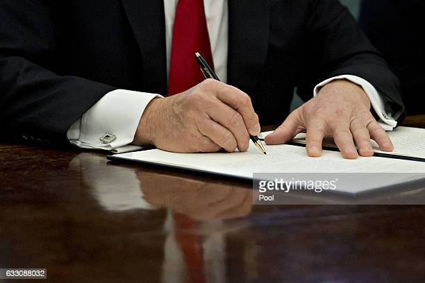 President Donald Trump signs an executive order in the Oval Office of the White House January 30, 2017 in Washington, DC. Trump said he will...