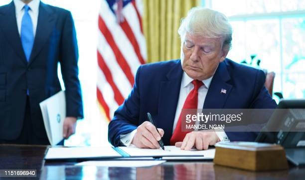 US President Donald Trump signs an executive order on Iran sanctions in the Oval Office of the White House on June 24 2019