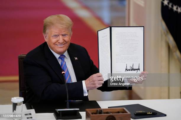 President Donald Trump signs an executive order related to reforming the hiring process for federal jobs in a meeting of the American Workforce...