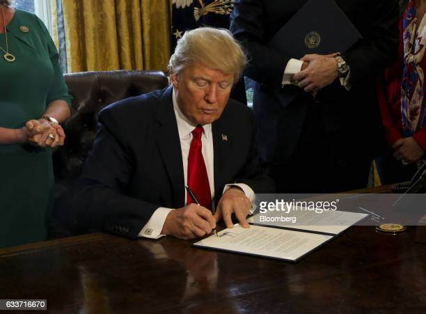 US President Donald Trump signs an Executive Order related to the review of the DoddFrank Act in the Oval Office of the White House in Washington DC...