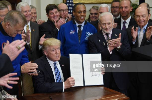 US President Donald Trump signs an Executive Order to reestablish the National Space Council as Apollo 11 astronaut Buzz Aldrin looks on in the...