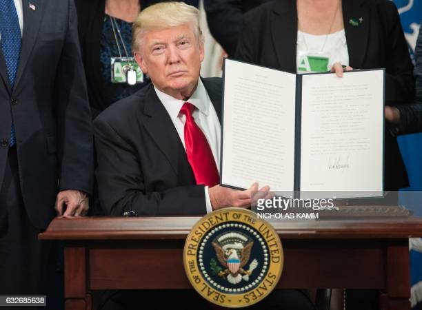 President Donald Trump signs an executive order to start the Mexico border wall project at the Department of Homeland Security facility in Washington...