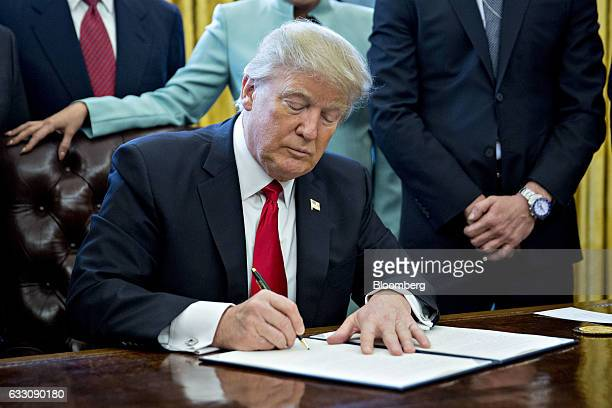 US President Donald Trump signs an executive order while surrounded by small business leaders in the Oval Office of the White House in Washington DC...
