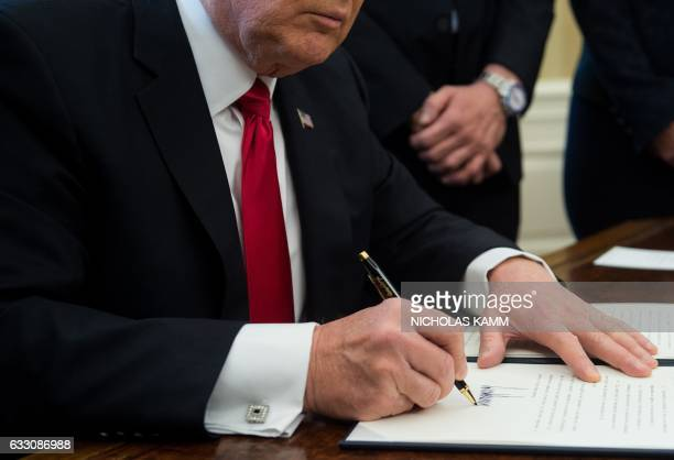 US President Donald Trump signs an executive order with small business leaders in the Oval Office at the White House in Washington DC on January 30...