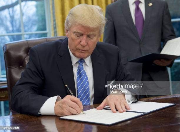 US President Donald Trump signs an executive order withdrawing the US from the TransPacific Partnership in the Oval Office of the White House in...