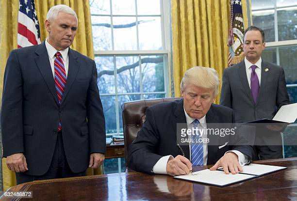 US President Donald Trump signs an executive order withdrawing the US from the TransPacific Partnership alongside US Vice President Mike Pence and...