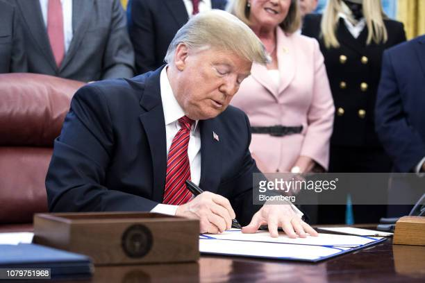US President Donald Trump signs antihuman trafficking legislation in the Oval Office at the White House in Washington DC US on Wednesday Jan 9 2019...