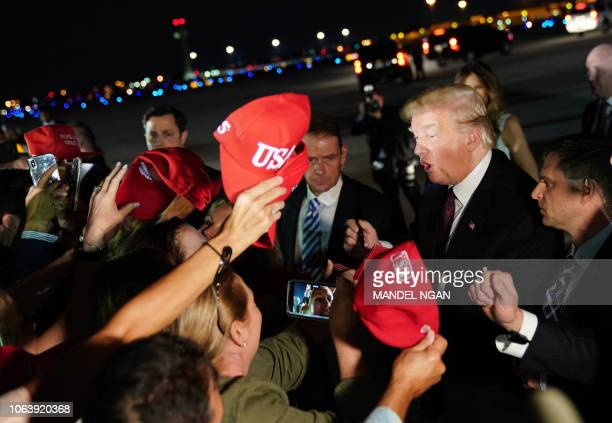 US President Donald Trump signs autographs as he arrives at Palm Beach International Airport in West Palm Beach Florida on November 20 2018 Trump and...