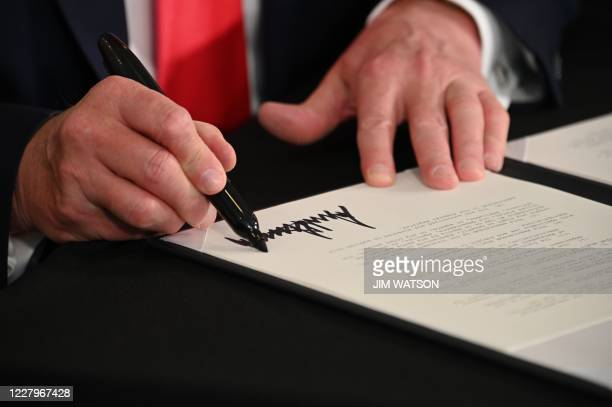 President Donald Trump signs executive orders extending coronavirus economic relief, during a news conference in Bedminster, New Jersey, on August 8,...