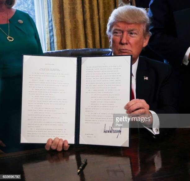 President Donald Trump signs Executive Orders in the Oval Office of the White House, including an order to review the Dodd-Frank Wall Street to roll...