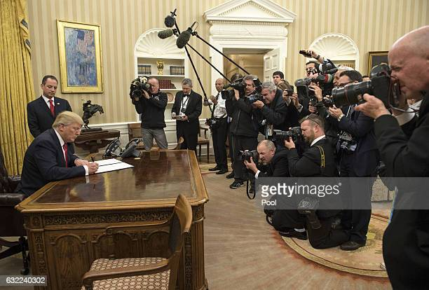 President Donald Trump signs his first executive order as president ordering federal agencies to ease the burden of President Barack Obama's...