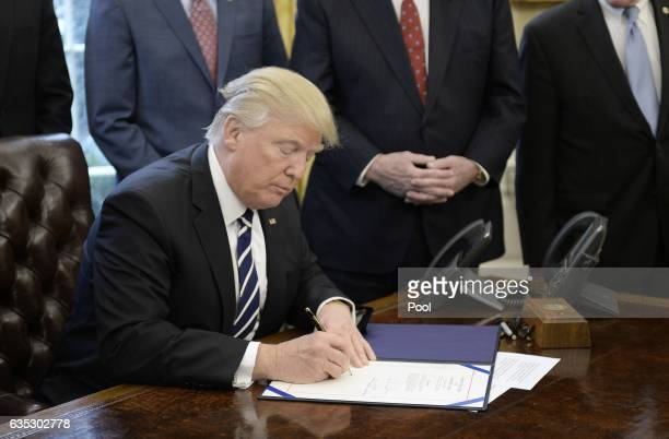 US President Donald Trump signs HJ Res 41 in the Oval Office of the White House on February 14 2017 in Washington DC The resolution nullifies a rule...