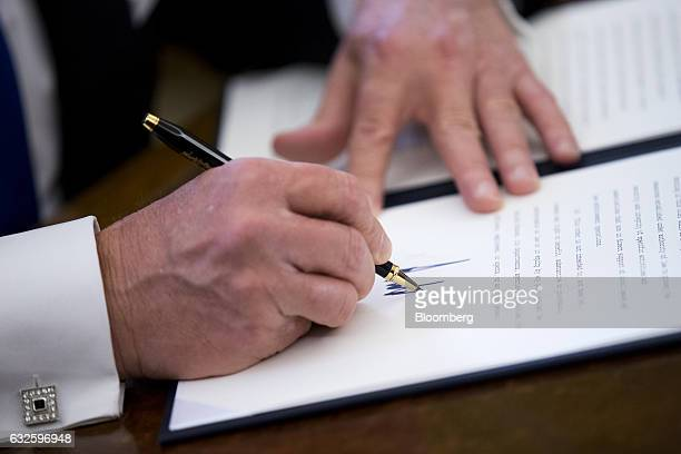 US President Donald Trump signs one of five executive orders related to the oil pipeline industry in the Oval Office of the White House in Washington...