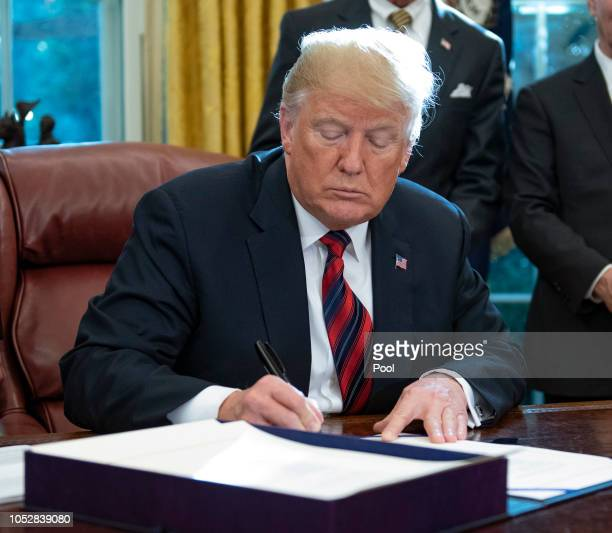 US President Donald Trump signs S3021 America's Water Infrastructure Act of 2018 in the Oval Office of the White House on October 23 2018 in...