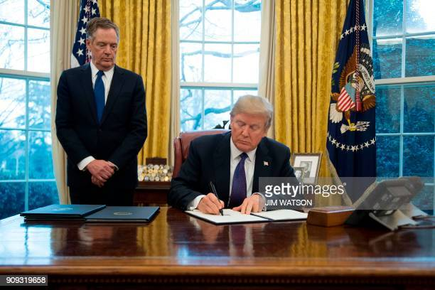US President Donald Trump signs Section 201 actions to impose tariffs with United States Trade Representative Robert Lighthizer in the Oval Office of...